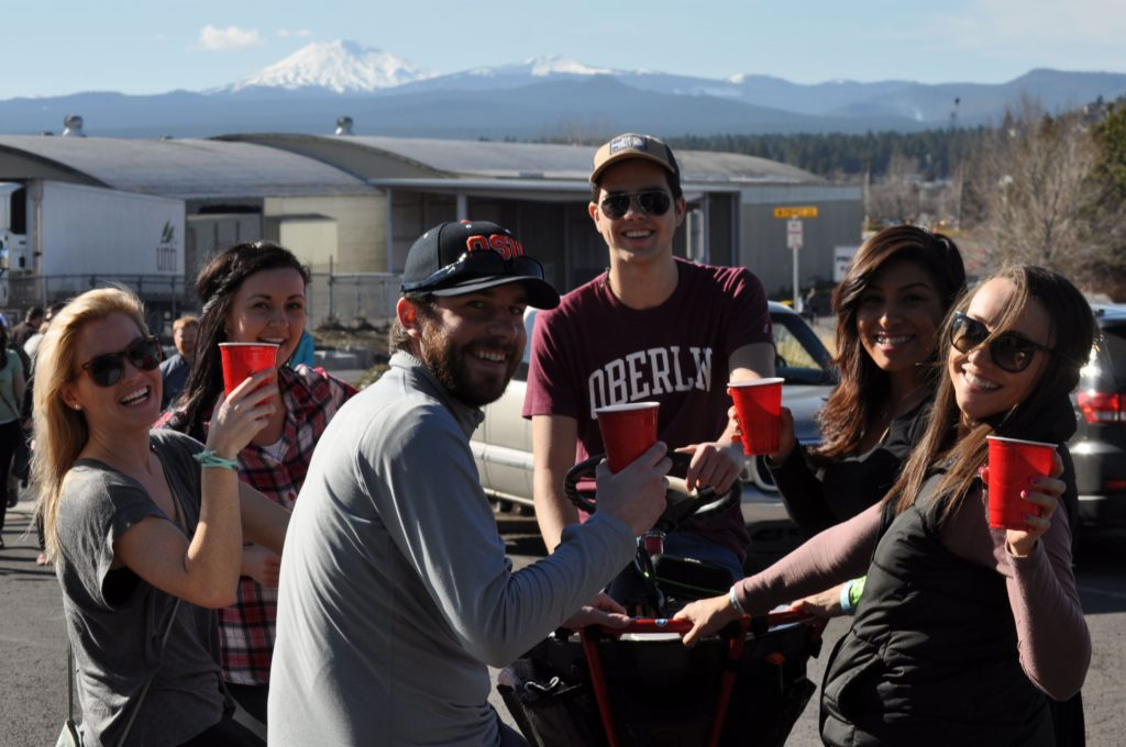 Folks hoisting pints on a cycle round with Mt. Bachelor in the background.
