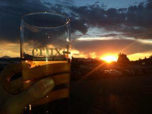 A Cascades sunset seen through a pint of golden ale from the parking lot at Crux Fermentation Project in Bend, Oregon
