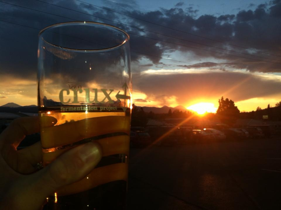 The Bend Tour Company Craft Beer Wine & Spirit Tasting Tour provides a brilliant Cascades sunset seen through a pint of golden ale from the parking lot at Crux Fermentation Project in Bend, Oregon
