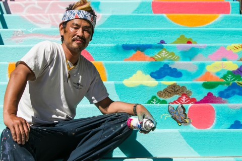 Yuya Negishi sitting on his stairway mural located next to the Regal Cinemas in Bend's Old Mill District a great art and culture stop.