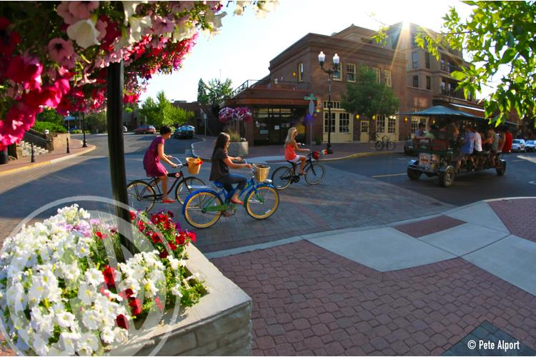 City sightseeing Bicyclist and Cycle Pub folks pedal down Minnesota Street on a lovely spring day in Bend, Oregon.