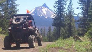 ATV tours heading down a trail toward a mountain peak